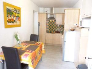Voici une photo de la cuisine avec table pour manger du studio n°C8 avec balcon donnant sur la rue Castellane. Cette location se trouve à 100 mètres des thermes.